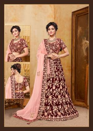 Be The Prettiest Bride Wearing This Very Beautiful And Heavy Embroidered Designer Bridal Lehenga Choli In Maroon Color Paired With Contrasting Light Peach Colored Blouse. This Lehenga Choli Is Velvet Based Paired With Net Fabricated Dupatta. Buy This Beautiful Lehenga Choli Now.