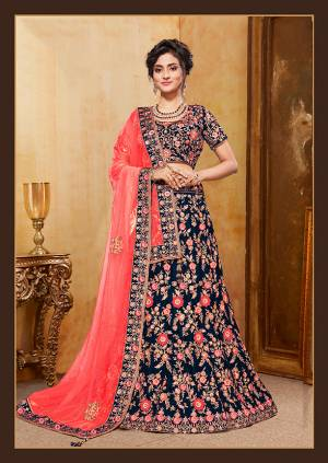 Get Ready For Your D-Day With This Heavy Designer Bridal Lehenga Choli In Dark Blue Color Paired With Contrasting Coral Red Colored Dupatta. Its Heavy Embroidered Blouse And Lehenga Are Fabricated On Velvet Paired With Net Fabricated Dupatta.