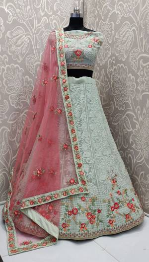 Here Is A Very Pretty Heavy Designer Lehenga Choli In Pastel Green Color Paired With Contrasting Pink Colored Dupatta. Its Blouse And Lehenga Are Fabricated On Georgette Beautified with Heavy Lakhnavi Embroidery Paired With Net Fabricated Dupatta.