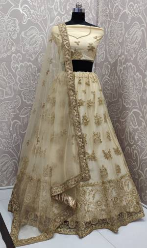 Get Ready For The Upcoming Wedding Season With This Very Beautiful And Heavy Designer Lehenga Choli In All Over Cream Color. This Heavy Embroidered Lehenga Choli Is Fabricated On Net Beautified With Tone To Tone Embroidery.