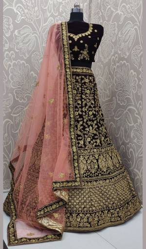 Here Is A Heavy Embroidered Designer Bridal Lehenga Choli For Your D-Day. This Heavy Velvet Based Lehenga Choli Is In Dark Maroon Color Paired With Baby Pink Colored Net Fabricated Dupatta. It Is Beautified With Heavy Jari And Coding Embroidery With Stone Work.