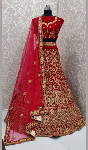 Here Is A Heavy Embroidered Designer Bridal Lehenga Choli For Your D-Day. This Heavy Velvet Based Lehenga Choli Is In Red Color Paired With Red Colored Net Fabricated Dupatta. It Is Beautified With Heavy Jari And Coding Embroidery With Stone Work.