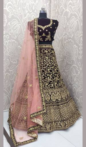Here Is A Heavy Embroidered Designer Bridal Lehenga Choli For Your D-Day. This Heavy Velvet Based Lehenga Choli Is In Dark Wine Color Paired With Baby Pink Colored Net Fabricated Dupatta. It Is Beautified With Heavy Jari And Coding Embroidery With Stone Work.