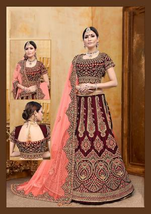 Be The Prettiest Bride Wearing This Very Beautiful And Heavy Embroidered Designer Bridal Lehenga Choli In Maroon Color Paired With Contrasting Dark Peach Colored Dupatta. This Lehenga Choli Is Velvet Based Paired With Net Fabricated Dupatta. Buy This Beautiful Lehenga Choli Now.