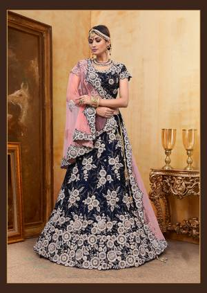 Be The Prettiest Bride Wearing This Very Beautiful And Heavy Embroidered Designer Bridal Lehenga Choli In Navy Blue Color Paired With Contrasting Baby Pink Colored Dupatta. This Lehenga Choli Is Velvet Based Paired With Net Fabricated Dupatta. Buy This Beautiful Lehenga Choli Now.