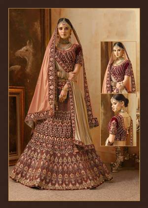 Be The Prettiest Bride Wearing This Very Beautiful And Heavy Embroidered Designer Bridal Lehenga Choli In Maroon Color Paired With Contrasting Peach Colored Dupatta. This Lehenga Choli Is Velvet Based Paired With Net Fabricated Dupatta. Buy This Beautiful Lehenga Choli Now.