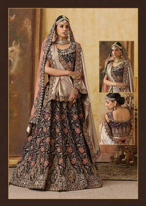 Get Ready For Your D-Day With This Heavy Designer Bridal Lehenga?Choli In Dark Wine Color Paired With Contrasting Baby Pink Colored Dupatta. Its Heavy Embroidered Blouse And Lehenga Are Fabricated On Velvet Paired With Net Fabricated Dupatta.