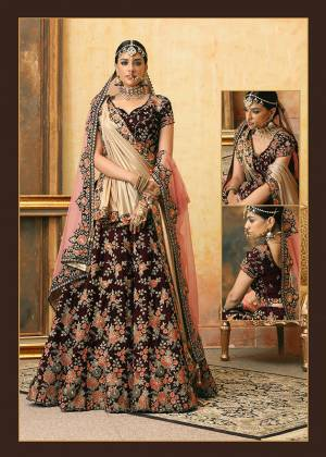 Get Ready For Your D-Day With This Heavy Designer Bridal Lehenga?Choli In Maroon Color Paired With Contrasting Peach Colored Dupatta. Its Heavy Embroidered Blouse And Lehenga Are Fabricated On Velvet Paired With Net Fabricated Dupatta