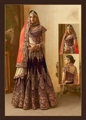 Be The Prettiest Bride Wearing This Very Beautiful And Heavy Embroidered Designer Bridal Lehenga Choli In Maroon Color Paired With Contrasting Orange Colored Dupatta. This Lehenga Choli Is Velvet Based Paired With Net Fabricated Dupatta. Buy This Beautiful Lehenga Choli Now