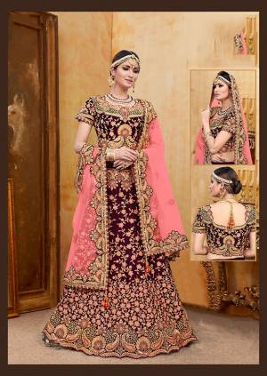 Get Ready For Your D-Day With This Heavy Designer Bridal Lehenga?Choli In Wine Color Paired With Contrasting Pink Colored Dupatta. Its Heavy Embroidered Blouse And Lehenga Are Fabricated On Velvet Paired With Net Fabricated Dupatta