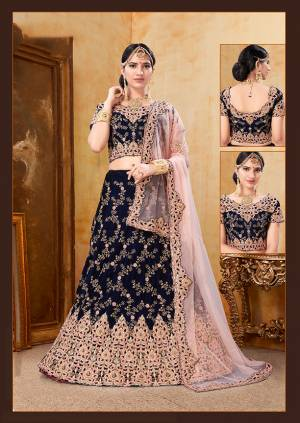 Get Ready For Your D-Day With This Heavy Designer Bridal Lehenga?Choli In Navy Blue Color Paired With Contrasting Baby Pink Colored Dupatta. Its Heavy Embroidered Blouse And Lehenga Are Fabricated On Velvet Paired With Net Fabricated Dupatta