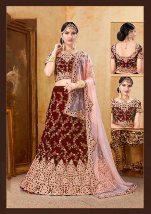 Be The Prettiest Bride Wearing This Very Beautiful And Heavy Embroidered Designer Bridal Lehenga Choli In Maroon Color Paired With Contrasting Baby Pink Colored Dupatta. This Lehenga Choli Is Velvet Based Paired With Net Fabricated Dupatta. Buy This Beautiful Lehenga Choli Now