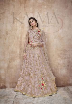 Flaunt Your Rich And Rich And Elegant Taste Wearing This Designer Heavy Floor Length Suit In All Over Pastel Pink. Its Heavy Embroidered Top Is Fabricated On Net Paired With Satin Silk Bottom And Net Fabricated Dupatta. Its Attractive Embroidery, Subtle Color And Designer Look Will Earn You Lots Of Compliments From Onlookers.