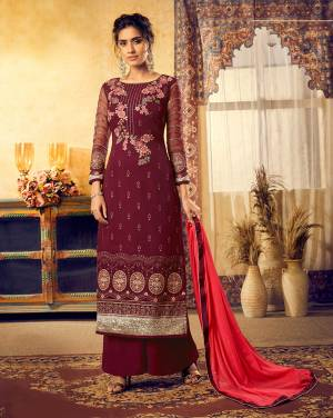 Here Is A Royal Looking Heavy Straight Suit In Maroon Color Paired With Red Colored Dupatta. Its Top Is Fabricated On Georgette Beautified With Heavy Embroidery Paired With Santoon Bottom And Chiffon Fabricated Dupatta.