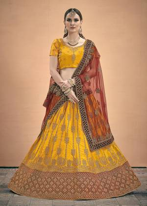 Get Ready For The Upcoming Wedding Season With This Heavy Designer Lehenga Choli In Musturd Yellow Color Paired With Contrasting Maroon Colored Dupatta. This Heavy Embroidered Lehenga Choli Is Satin Based Paired With Net Fabricated Dupatta. Buy Now.