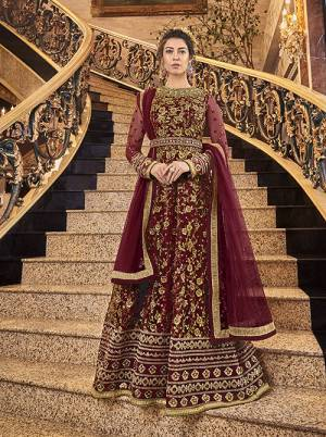 Here Is A Royal Looking Heavy Designer Floor Length Suit In Maroon Color. Its Heavy Embroidered Top Is Fabricated On Net Paired With Art Silk Fabricated Bottom And Net Fabricated Dupatta. Its Royal Color and Pattern Will Earn You Lots Of Compliments From Onlookers.