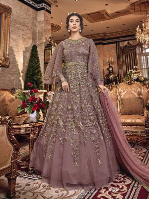 New Shade In Purple Is Here With This Heavy Designer Floor Length Suit In Mauve Color. This Beautiful Patterned And Heavy Embroidered Floor Length Top Is Fabricated On Net Paired With Santoon Bottom And Net Fabricated Dupatta. Buy Now.