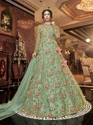 Add This Beautiful Designer Floor Length Suit To Your Wardrobe With A Quite Unique Pattern In Light Green Color. Its Top IS Fabricated On Net Paired With Muslin Bottom And Net Fabricated Dupatta. Its Top Is Beautified With Contrasting Work Which Gives A Attractive Look To The Dress.