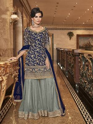 Bold And Elegant Color Pallete IS Here With This Designer Sharara Suit In Navy Blue Colored Top And Dupatta Paired With Contrasting Grey Coloree Bottom. Its Top, Bottom And Dupatta Are Fabricated On Net Beautified With Heavy Embroidery. Buy Now.