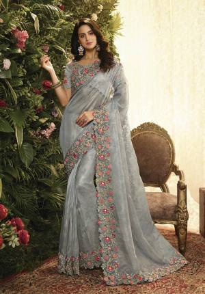 This Wedding Season, Look The Most Elegant Of All Wearing This Heavy Designer Saree In Grey Color. This Heavy Contrasting Embroidered Saree Is Fabricated On Orgenza Paired With Art Silk Fabricated Blouse.