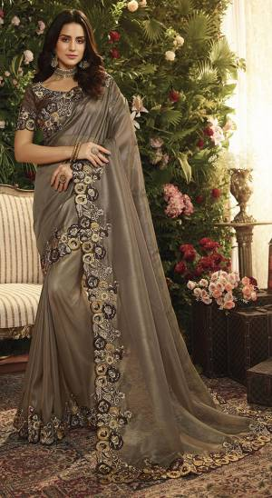 For A Bold And Beautiful Look, Grab This Heavy Designer Saree In Dark Grey Color Paired With Dark Brown Colored Blouse. This Saree Is Fabricated On Orgenza Paired With Art Silk Fabricated Blouse. It Is Beautified With Heavy Embroidered Lace Border.