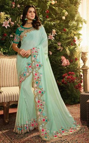 Grab This Very Beautiful And Elegant Looking Heavy Designer Saree In Turquoise Blue Color Paired With Contrasting Teal Green Colored Blouse. Ths Saree Is Fabricated On Art Silk And Net Paired With Art Silk Fabricated Blouse. It Has Pretty Contrasting Embroidery Giving An Enhanced Look.