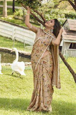 Celebrate This Festive Season With Beauty And Comfort Wearing This Lovely Floral Printed Saree In Beige Color Paired With Beige Colored Blouse. This Silk Based Saree Is Light Weight And Also Gives A Rich Look.