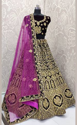 Here Is a Proper Heavy Traditional Lehenga Choli For The Upcoming Wedding Season In Dark Wine Color Paired with A Very Pretty Magenta Pink Colored Dupatta. This Heavy Embroidered Designer Lehenga Choli Is Fabricated On Velvet Paired With Net Fabricated Dupatta. Buy This Beautiful Traditional Piece Now.