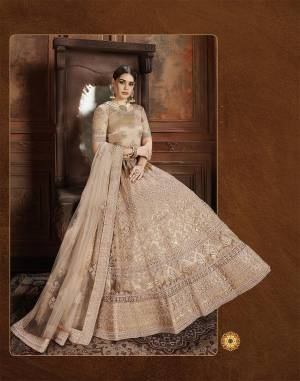 Get Ready For The Upcoming Wedding Season With This Very Beautiful Heavy Designer Lehenga Choli In Beige Color. Its Heavy Embroidered Blouse, Lehenga And Choli Are Fabricated On Net Which Is Light In Weight And Easy To Carry Throughout The Gala.