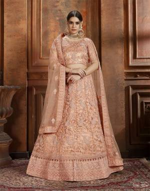 Get Ready For The Upcoming Wedding Season With This Very Beautiful Heavy Designer Lehenga Choli In Dark Peach Color. Its Heavy Embroidered Blouse, Lehenga And Choli Are Fabricated On Net Which Is Light In Weight And Easy To Carry Throughout The Gala.