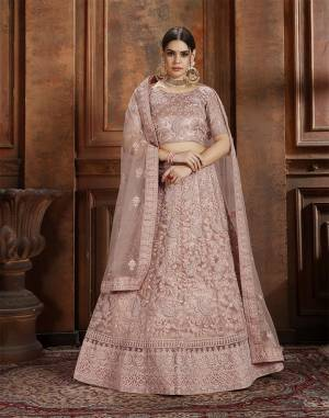 Get Ready For The Upcoming Wedding Season With This Very Beautiful Heavy Designer Lehenga Choli In Dusty Pink Color. Its Heavy Embroidered Blouse, Lehenga And Choli Are Fabricated On Net Which Is Light In Weight And Easy To Carry Throughout The Gala.