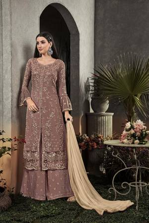 Here Is A Very Beautiful Designer Straight Suit In Pretty Mauve Color Paired With Cream Colored Dupatta. Its Pretty Embroidered Top And Bottom Are Fabricated On Georgette Paired With Chiffon Fabricated Dupatta. It Is Light In Weight And Easy To Carry All Day Long.