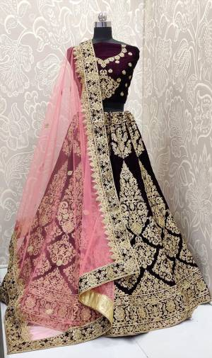 Here Is A Beautiful Designer Bridal Lehenga Choli In Dark Purple Color Paired With Baby Pink Colored Dupatta. This Beautiful Heavy Lehenga Choli Is Fabricated On Velvet Paired With Net Fabricated Dupatta. It Is Beautified With Heavy Detailed Embroidery. Get Ready For Your D-Day With This Designer Piece And Look The Most Graceful Of All.