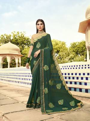 Celebrate This Festive Season With Beauty And Comfort Wearing This Heavy Designer Saree In Pine Green Color Paired With Cream Colored Blouse. This Saree Is Chiffon Based Paired With art Silk Fabricated Blouse. It Is Light In Weight And Easy To Carry All Day Long.