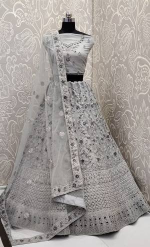 This Wedding Season, Look The Most Graceful Of All Wearing This Heavy Designer Elegant Lehenga Choli In Grey Color. Its Blouse, Lehenga And Dupatta are Fabricated on Net Beautified With Tone To Tone Coding And Resham Embroidery With Stone Work. Its Pretty Elegant Color And Tone-To-Tone Work Will Definitely Earn You Lots Of Compliments From Onlookers.