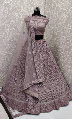 This Wedding Season, Look The Most Graceful Of All Wearing This Heavy Designer Elegant Lehenga Choli In Mauve Color. Its Blouse, Lehenga And Dupatta are Fabricated on Net Beautified With Tone To Tone Coding And Resham Embroidery With Stone Work. Its Pretty Elegant Color And Tone-To-Tone Work Will Definitely Earn You Lots Of Compliments From Onlookers.
