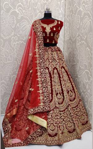 Here Is A Beautiful Designer Bridal Lehenga Choli In Maroon Color?Paired With Red Colored Dupatta. This Beautiful Heavy Lehenga Choli Is Fabricated On Velvet Paired With Net Fabricated Dupatta. It Is Beautified With Heavy Detailed Embroidery. Get Ready For Your D-Day With This Designer Piece And Look The Most Graceful Of All.