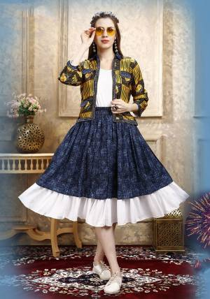 Here Is A Pretty Three Piece Western Set In White Colored Top Paired With Blue Colored Skirt And Yellow Colored Printed Jacket. Its Top Is Fabricated on Cotton Lycra Paired With Rayon Fabricated Skirt and Jacket.