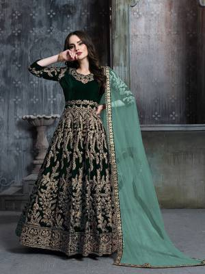 Get Ready For The Upcoming Wedding And Festive Season Wearing This Heavy Designer Floor Length Suit  In Dark Green Color Paired With Light Green Colored Dupatta. Its Heavy Embroidered Top Is Fabricated on Velvet Paired With Santoon Bottom And Net Fabricated Dupatta.