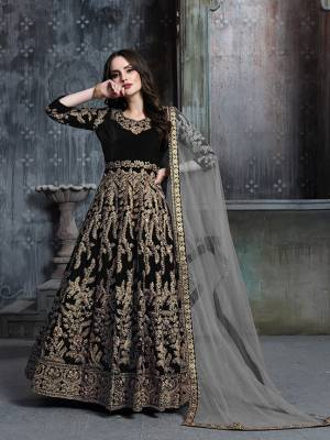 Get Ready For The Upcoming Wedding And Festive Season Wearing This Heavy Designer Floor Length Suit  In Black Color Paired With Grey Colored Dupatta. Its Heavy Embroidered Top Is Fabricated on Velvet Paired With Santoon Bottom And Net Fabricated Dupatta.