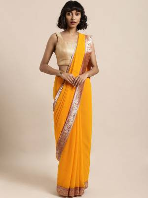 Celebrate This Festive Season In This Pretty Saree In Yellow Color Paired With Red Colored Blouse, This Pretty Saree Is Georgette Based Paired With Art Silk Fabricated Blouse. It Is Light In Weight And Easy To Carry All Day Long.