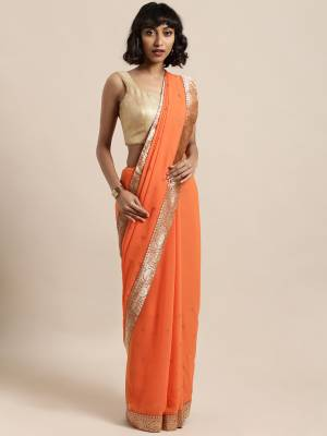 Celebrate This Festive Season In This Pretty Saree In Orange Color Paired With Red Colored Blouse, This Pretty Saree Is Georgette Based Paired With Art Silk Fabricated Blouse. It Is Light In Weight And Easy To Carry All Day Long.