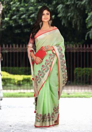 Flaunt Your Rich And Elegant Taste Wearing This Pretty Saree In Light Green Color Paired With Red Colored Blouse. This Saree And Blouse Are Fabricated On Linen Beautified With Floral Weave. It Is Light In Weight And Gives A Rich Look To Your Personality.
