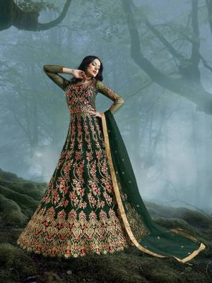 Grab This Heavy Designer Floor Length Suit In Dark Green Color For The Upcoming Wedding Season. This Very Beautiful And Heavy Embroidered Floor Length Top Is Fabricated On Net Paired With Silk based Bottom And Net Fabricated Dupatta. Its Detailed Embroidery With Perfect Color Combination Will Earn You Lots Of Compliments From Onlookers.
