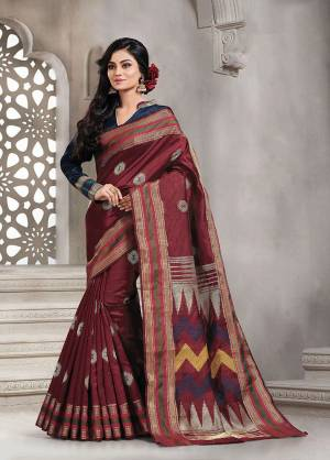 Add This Pretty Rich And Elegant Looking Saree In Maroon Color Paired With Contrasting Navy Blue Colored Blouse. This Saree And Blouse are Handloom Silk Based Beautified With Weave. Buy This Saree Now.
