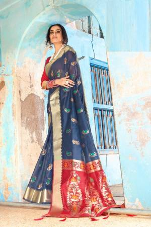 Shine Bright Wearing This Attractive Looking Saree In Navy Blue Color Paired With Contrasting Red Colored Blouse. This Saree And Blouse Are Fabricated On Cotton Silk Beautified With Weave. Buy This Saree Now.
