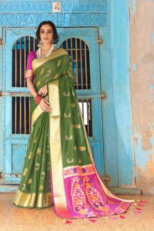 Flaunt Your Rich And Elegant Taste Wearing This Lovely Silk Based Saree In Olive Green Color Paired With Contrasting Pink Colored Blouse. This Saree And Blouse Are Fabricated On Cotton Silk Beautified With Weave. Buy Now.