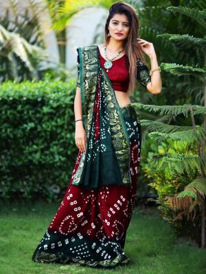 Here Is A Beautiful Bandhej Designer Saree In Maroon And Pine Green Color. This Saree And Blouse Are Fabricated On Art Silk Which Also Gives A Rich Look To Your Personality. Buy Now.