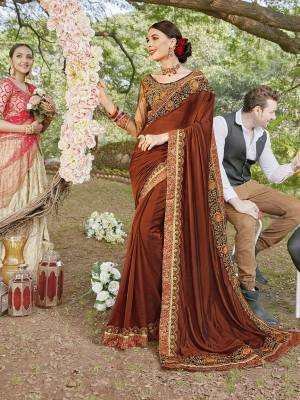 Go With The Lovely Shades Of Brown Wearing This Heavy Designer Saree In Brown Color Paired With Dark Brown Colored Blouse. This Saree Is Satin Georgette Based Paired With Art Silk And Net Fabricated Blouse.
