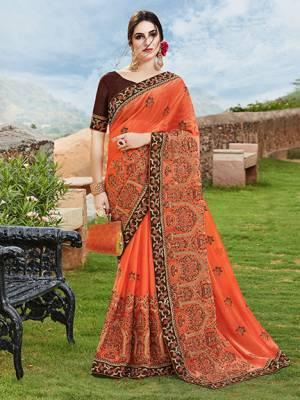 Get Ready For The Upcoming Wedding And Festive Season With This Designer Saree In Orange Color Paired With Contrasting Brown Colored Blouse. This Heavy Embroidered Saree Is Chiffon Silk Based Paired With Art Silk Fabricated Blouse.